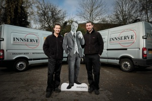Full size cut-out of fictional character Rupert Lovebeer with Innserve technicians.