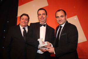 Andy Davies, business development manager for indoor controls at Harvard Engineering, centre, collects the Lux Award for Controls Innovation of the Year for EyeNut from, left, comedian John Molony and, right, presenter Simon Reed, UK Country sales manager of Eaton's Cooper Lighting and Safety.